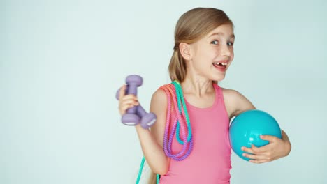 Girl-Holding-Dumbbells-And-Skipping-Rope-And-Ball-On-The-White-Background