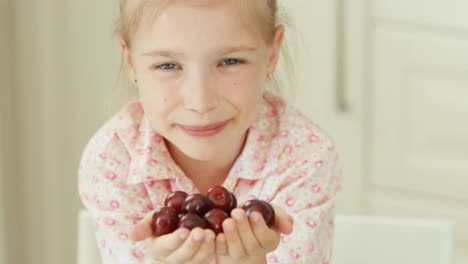 Girl-Holding-Handful-Of-Cherries-And-Laughing-At-The-Camera