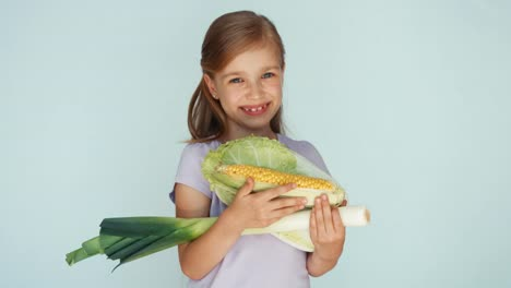 Girl-Holding-Vegetables-Cabbage-Corn-Celery-And-Laughing-At-Camera