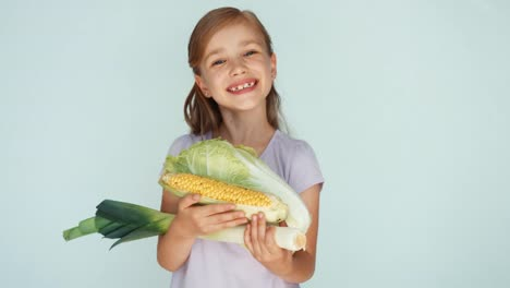 Girl-Holding-Vegetables-Cabbage-Corn-Celery-And-Smiling-At-Camera