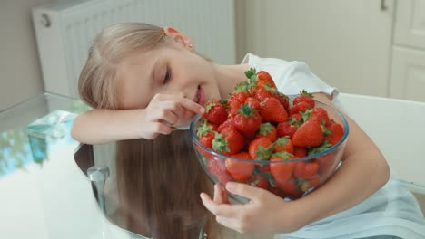 Girl-Hugging-Big-Plate-Of-Strawberries-And-Looking-At-Camera