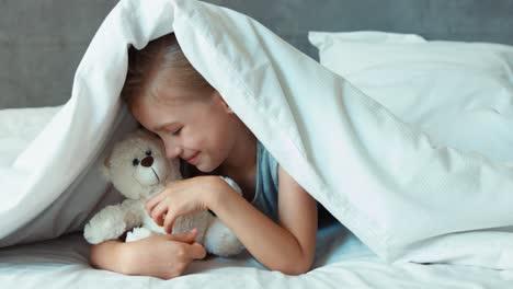 Mädchen-Das-Teddybären-Unter-Der-Decke-Umarmt-Und-In-Die-Kamera-Lächelt