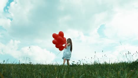 Girl-In-A-White-Dress-Holding-Red-Balloons-And-Whirling-On-A-Green-Grass-01