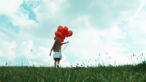 Girl-In-A-White-Dress-With-Balloons-Walking-On-The-Grass