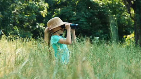 Girl-In-The-Grass-Looking-Through-Binoculars-At-Distance