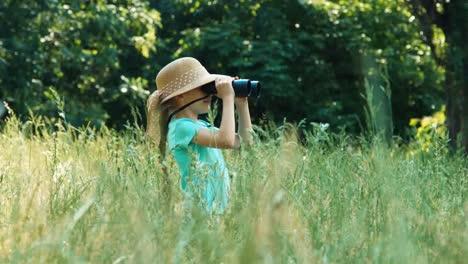 Mädchen-Im-Gras-Das-Aus-Der-Ferne-Durch-Ein-Fernglas-Schaut