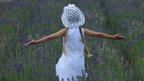 Girl-In-White-Dress-Is-Spinning-In-Field-Of-Flowers