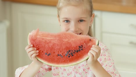 Girl-Is-Holding-A-Big-Piece-Of-Watermelon-And-Sniffs-It-And-Smiling
