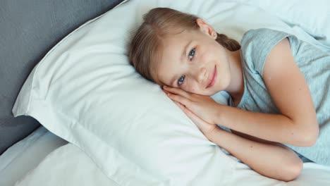 Mädchen-Ist-In-Einem-Bett-Und-Lächelt-Draufsicht
