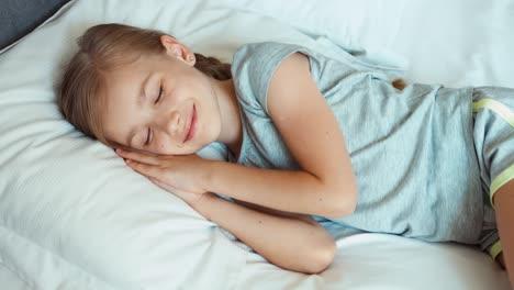 Mädchen-Liegt-In-Einem-Bett-Und-Wacht-Auf-Und-Lächelt