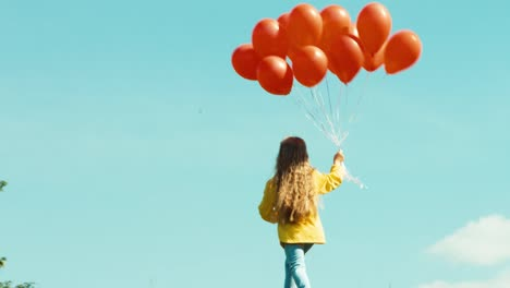 Girl-Is-In-Yellow-Raincoat-Running-With-Red-Balloons-On-The-Field