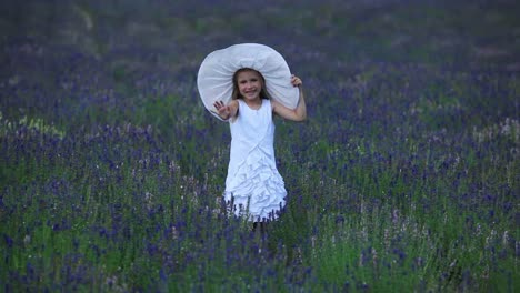 Girl-Is-Standing-In-Violet-Flowers-Portrait-Happy-Little-Girl-Waving-A-Hand