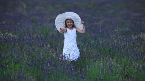 Niña-Está-De-Pie-En-Flores-Violetas-Retrato-Feliz-Niña-Agitando-Una-Mano
