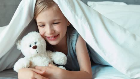 Girl-Kissing-Teddy-Bear-Child-Is-Under-The-Blanket-Zooming