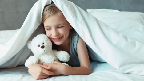 Girl-Kissing-Teddy-Bear-Child-Is-Under-The-Blanket