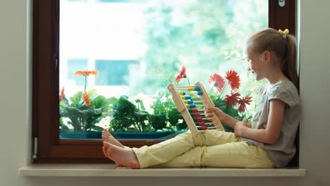 Girl-Learning-To-Count-With-Abacus-And-Sitting-On-The-Sill-Thumbs-Up-Ok