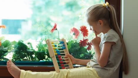 Girl-Learning-To-Count-With-Abacus-And-Sitting-On-The-Sill-Zooming