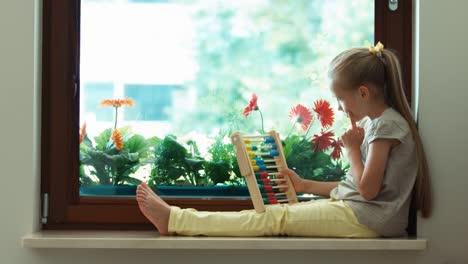 Mädchen-Lernt-Mit-Abakus-Zu-Zählen-Und-Sitzt-Auf-Dem-Fensterbrett