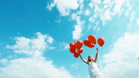 Girl-letting-go-of-balloons-and-watching-them-fly-into-the-sky