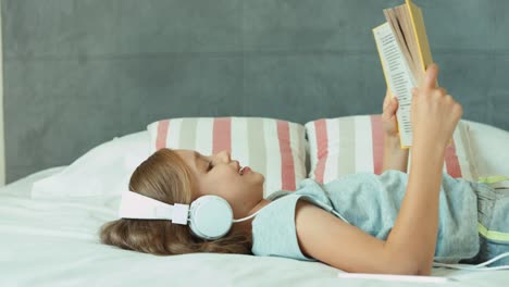 Girl-Listening-Music-In-Headphones-And-Reading-Book-Child-Lying-Resting