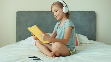 Girl-Listening-Music-In-Headphones-And-Reading-Book-Child-Resting