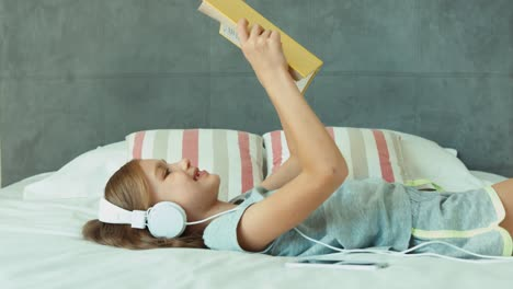 Girl-Listening-Music-In-Headphones-And-Reading-Hugging-Book