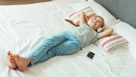 Girl-Listening-Music-In-White-Headphones-And-Lying-On-The-Bed