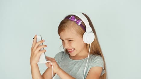 Girl-Listening-To-Music-With-A-Smartphone-And-Dancing-On-A-White-Background