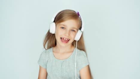 Girl-Listening-To-Music-With-Headphones-And-Dancing-On-A-White-Background