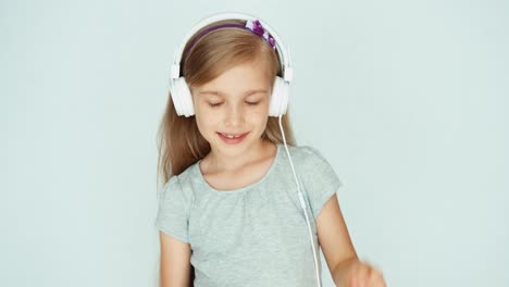 Girl-Listening-To-Music-With-Headphones-On-A-White-Background