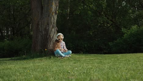 Girl-listening-to-music-on-her-phone-under-a-tree-6