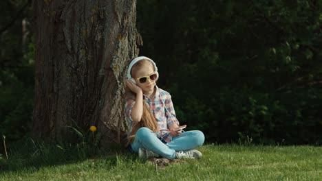 Niña-Escuchando-Música-Niño-Sentado-Bajo-Un-árbol