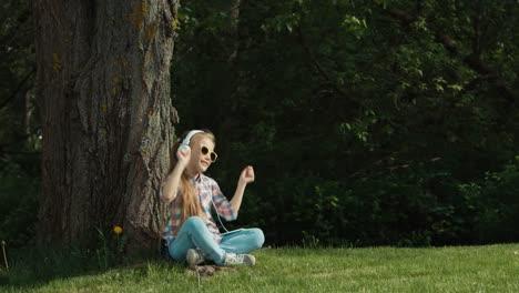 Niña-Escuchando-Música-Niña-Baila-Mientras-Está-Sentado-Bajo-Un-árbol