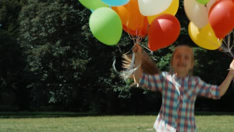 Girl-Looking-Out-From-Behind-The-Balloons-And-Jumping-And-Laughing