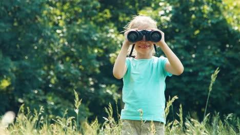 Mädchen-Das-Durch-Ein-Fernglas-In-Die-Kamera-Schaut-Und-Mit-Der-Hand-Winkt-Und-Lachend-Zoomt