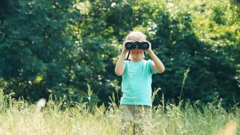 Mädchen-Schaut-Durch-Ein-Fernglas-In-Die-Kamera-Und-Winkt-Mit-Der-Hand-Wa