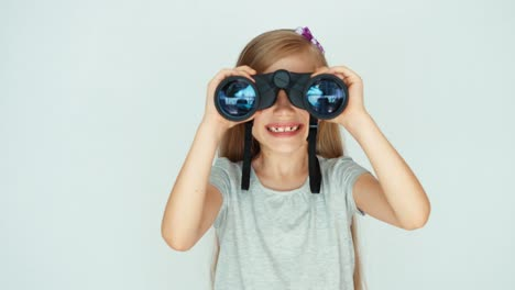 Girl-Looking-Through-Binoculars-At-Camera-On-A-White-Background