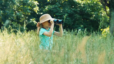 Girl-Looking-Through-Binoculars-At-Distance-Child-Turns-On-The-Camera