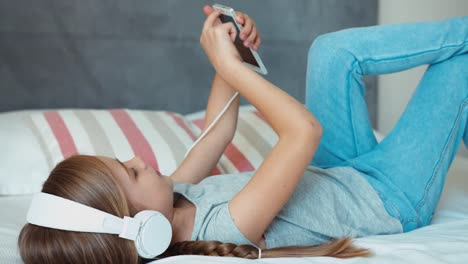 Girl-Lying-Resting-On-The-Bed-And-Listening-Music-In-Headphones-And-Is-Online