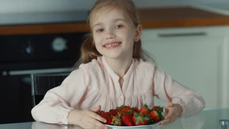 Girl-Pulling-The-Large-Plate-Of-Strawberries-And-Looking-At-Camera