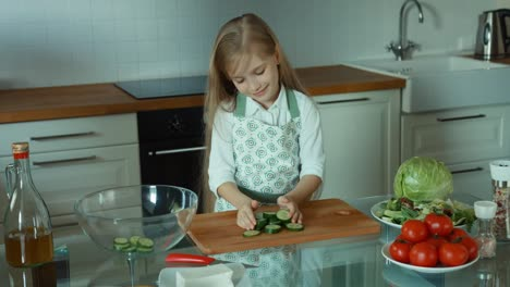 Girl-Putting-Sliced-Cucumber-In-A-Bowl