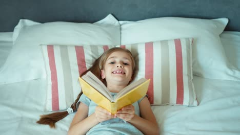 Girl-Reading-Book-Child-Lying-On-The-Bed-And-Smiling-At-Camera