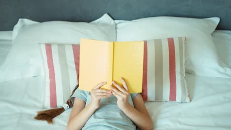 Girl-Reading-Book-Child-Lying-Resting-On-The-Bed-And-Smiling-At-Camera
