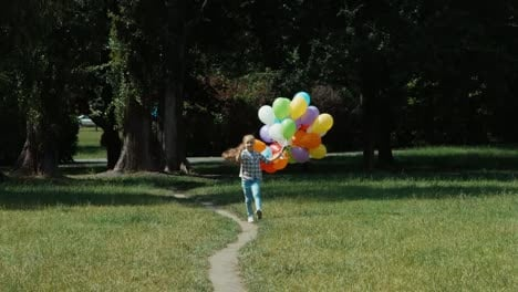 Girl-Running-With-Balloons-In-The-Meadow-At-Camera