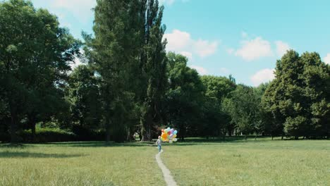 Girl-Running-With-Balloons-On-A-Footpath-In-The-Meadow-At-Camera-02