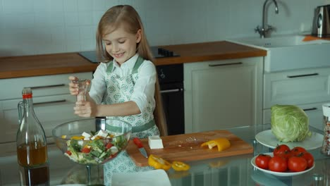 Child-Chef-In-The-Kitchen-Girl-Sprinkles-Salt-On-The-Salad