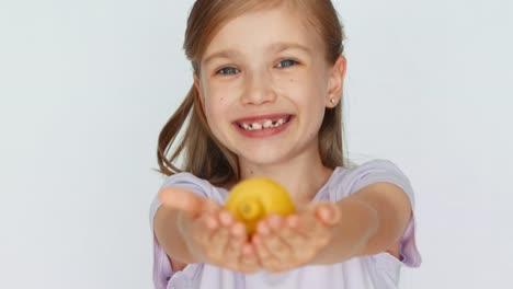 Girl-Showing-And-Advertises-Lemon-And-Smiling-At-Camera-Closeup