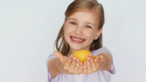 Girl-Showing-Lemon-Child-Laughing-At-Camera-Closeup
