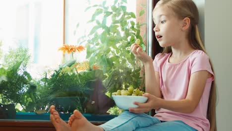 Girl-Sitting-On-A-Windowsill-And-Eating-Gooseberries-Zooming