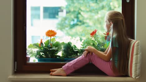 Girl-Sitting-On-The-Windowsill-And-Looking-In-Window-And-Smiling-At-Camera-02